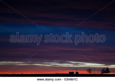 Un grande cielo tramonto su una fattoria in silhouette in Texas Panhandle. Foto Stock