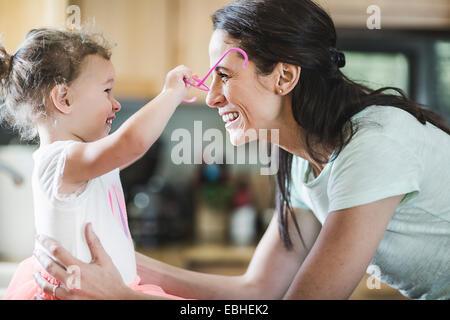 Madre e figlia giocando in cucina Foto Stock