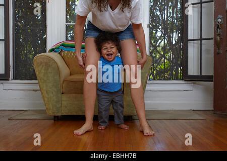 Bimbi maschio prendendo i primi passi con la madre in salotto Foto Stock