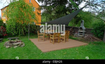 Con giardino coperto tavola con molte sedie in un giardino ornamentale Foto Stock