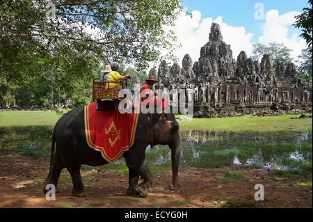 ANGKOR Wat, Cambogia - 30 ottobre 2014: turisti cavalcare un elefante su una sedia howdah, una pratica controversa. Foto Stock