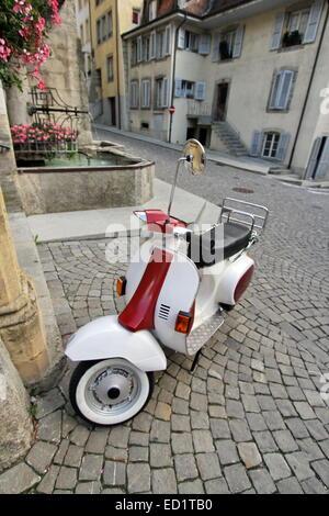Classico bianco e rosso scooter parcheggiato in stretta strada vecchia di Estavayer-le-Lac, cantone di Friburgo, Foto Stock