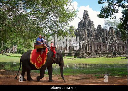 ANGKOR Wat, Cambogia - 30 ottobre 2014: i turisti di marcia elefante su una sedia howdah, una pratica controversa Foto Stock