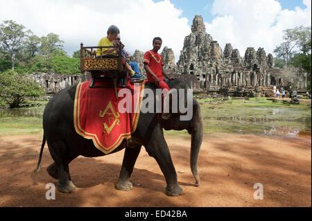 ANGKOR Wat, Cambogia - 30 ottobre 2014: turisti cavalcare un elefante su una sedia howdah, un controverso e pratica Foto Stock