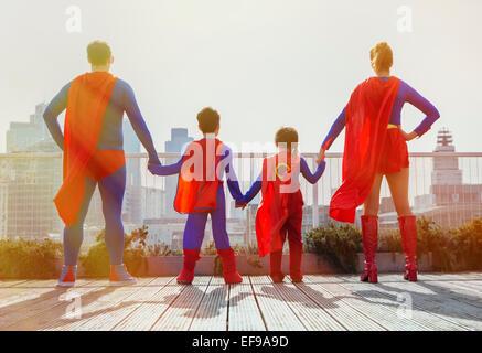 Famiglia di supereroi in piedi sul tetto della città Foto Stock