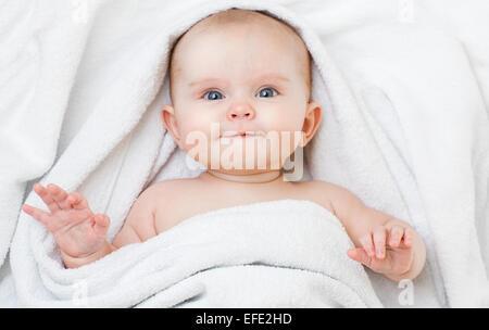 Carino sorridente divertenti baby sdraiato sulla schiena in asciugamano di balneazione Foto Stock