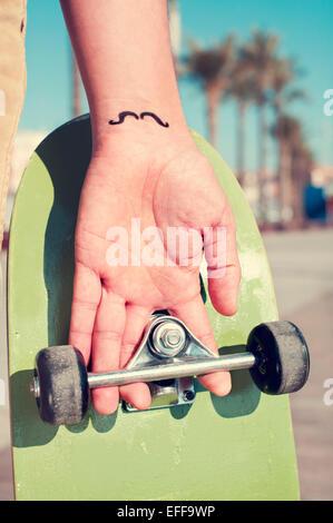 Primo piano di un giovane uomo con i baffi tatuati nel suo polso tenendo uno skateboard Foto Stock