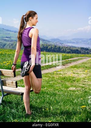 Foto di una giovane donna di allungamento della gamba di lei prima che Lei comincia a correre su un percorso di Foto Stock