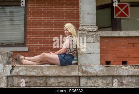 Un 17-anno-vecchio ragazzo caucasico con capelli biondi indossa pantaloni corti e maglietta floreale si siede contro Foto Stock