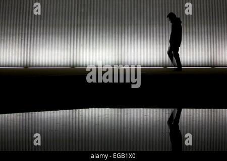 Lonely Man camminare sotto un ponte/tunnel Foto Stock