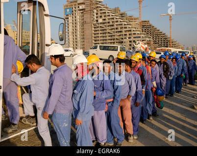 Lavoratori edili accodamento per salire su un autobus a quarti viventi al termine della giornata lavorativa in Dubai Foto Stock