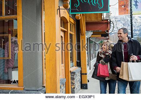 Giovane con le borse della spesa al di fuori della vetrina Foto Stock