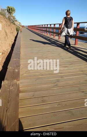 Donna che cammina sulla passerella di legno, lungomare, collegando le spiagge della Costa del Sol, La Cala, Andalusia, Foto Stock