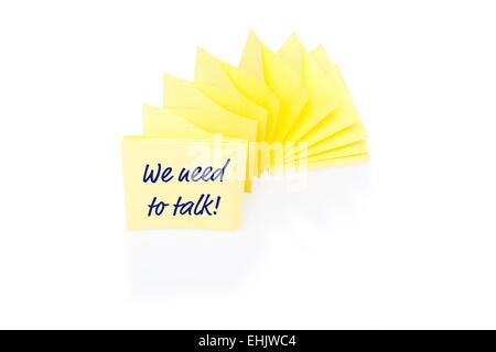 Bigliettino giallo sul blocco con il messaggio di cui abbiamo bisogno per parlare Foto Stock