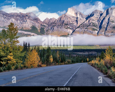 Road, nebbia e nuvole basse con colori autunnali. Il Parco Nazionale di Banff. Lo stato di Alberta, Canada Foto Stock