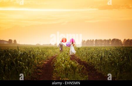 Felice giovani sposi in esecuzione sul campo al tramonto con grande e luminosa palloncini colorati Foto Stock