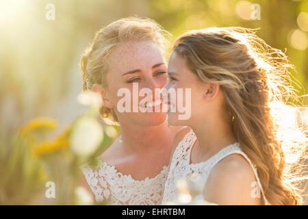 Sposa parlando di damigella nel giardino interno Foto Stock
