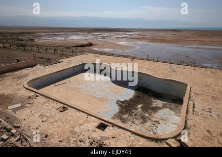 Vista della costa del mar Morto dal Giordano abbandonati Lido hotel che di recente è crollato a causa di sinkholes Foto Stock