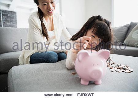 Madre guarda la figlia deposito moneta nel salvadanaio Foto Stock