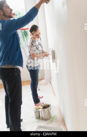 Sorridente giovane pittura parete Foto Stock