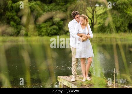 Romantico coppia giovane in piedi vicino al fiume Foto Stock