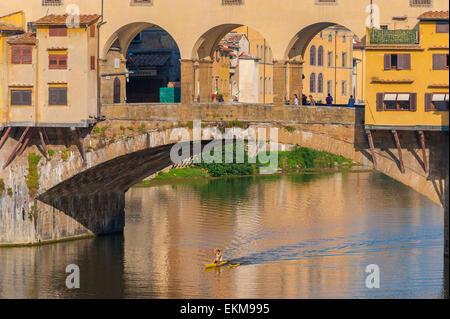 Firenze estate fiume Arno, la vista di un uomo a bordo di una canoa canottaggio sotto il Ponte Vecchio a Firenze, Foto Stock