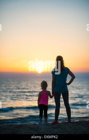 Silhouette di madre e bambina sulla spiaggia cercando in distanza. vista posteriore Foto Stock
