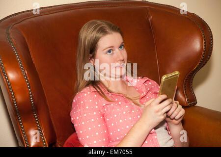Ragazza adolescente utilizzando iPhone cellulare dispositivo in interni signor © Myrleen Pearson Foto Stock