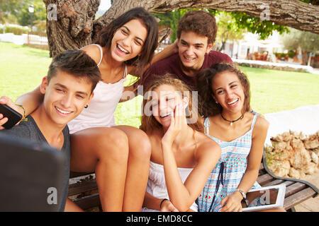 Gruppo di adolescenti seduti su un banco di lavoro tenendo Selfie in posizione di parcheggio Foto Stock