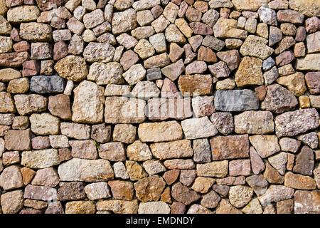 Pietre di diverse forme, dimensioni e colori in una pietra a secco sul muro di un edificio. Regno Unito, Gran Bretagna Foto Stock