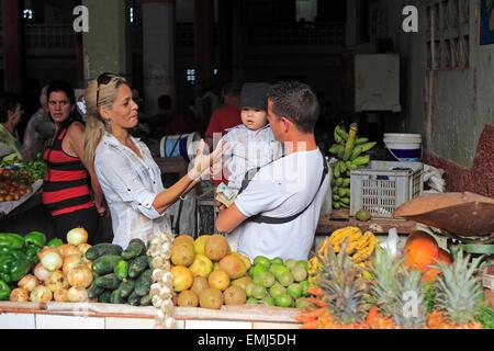 Giovane famiglia cubana nel mercato di frutta e verdura che mostra i prodotti disponibili per la vendita a Cienfuegos Foto Stock