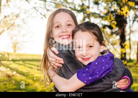 Sorelle sorriso abbraccio Foto Stock