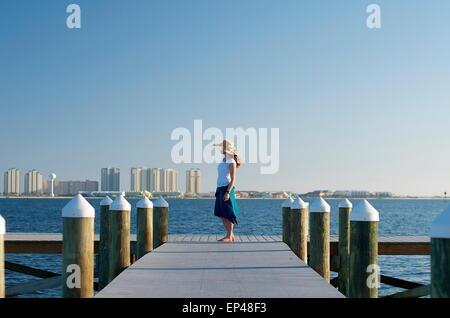 La donna nel cappello per il sole in piedi alla fine di un molo, Florida, Stati Uniti d'America Foto Stock