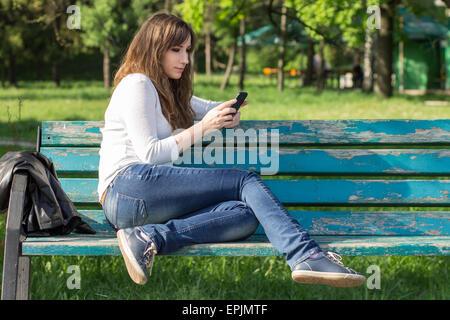 Piuttosto giovane donna utilizza lo smartphone seduto sulla panchina nel parco al giorno d'estate. Ragazza di appoggio Foto Stock