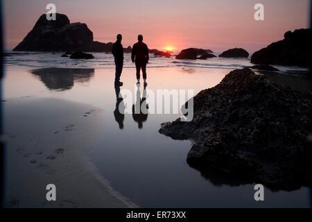 La gente guarda il tramonto sul mare di pile sulla spiaggia di Trinidad Bay in California costiera Monumento Nazionale Foto Stock