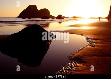 La gente a piedi lungo la spiaggia al tramonto sul mare di pile su Trinidad Bay in California costiera Monumento Foto Stock