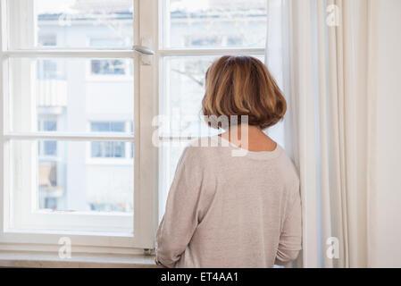Vista posteriore della donna senior di guardare attraverso una finestra, Monaco di Baviera, Germania Foto Stock