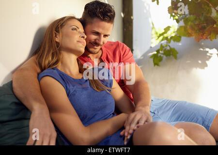 Colpo all'aperto di romantica coppia giovane seduti insieme sul lettino in cortile. Giovane uomo e donna innamorata Foto Stock