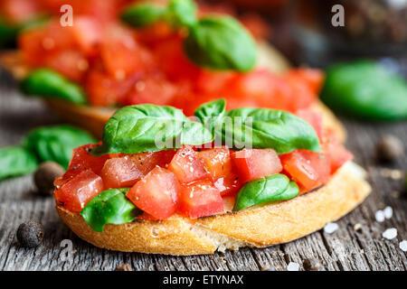 Bruschetta di pomodoro con un trito di pomodori e basilico sul pane tostato Foto Stock