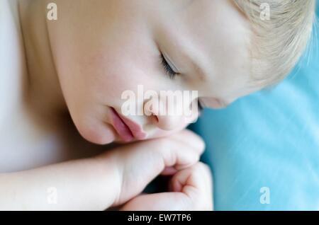 Close-up di un ragazzo che dorme con le mani in una forma di cuore Foto Stock