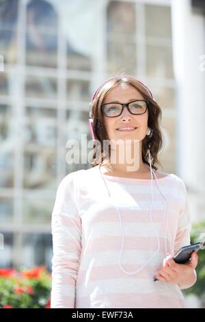 Premurosa donna che guarda lontano mentre ascolti musica all'aperto Foto Stock