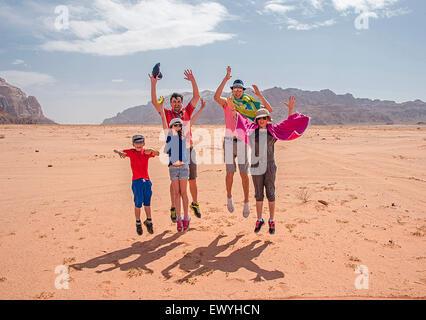 La famiglia felice del salto in aria di Wadi Rum, Aqaba Giordania Foto Stock