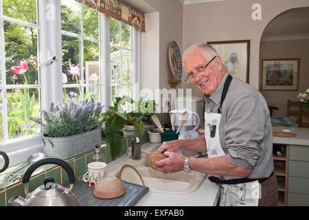 Senior uomo in cucina, lavaggio piatti Foto Stock