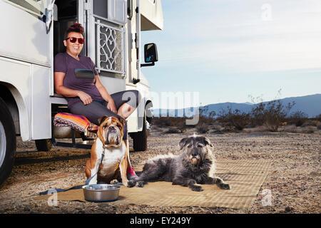 Ritratto di metà donna adulta e due cani seduti sul camper passo, Borrego Springs, California, Stati Uniti d'America Foto Stock