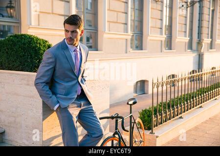 Imprenditore bello in piedi all'aperto in città Foto Stock