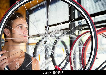 Giovane uomo esaminando i raggi della ruota in negozio di biciclette Foto Stock