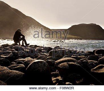 Uomo seduto sulle rocce e guardando il mare in Giant's Causeway, Irlanda Foto Stock