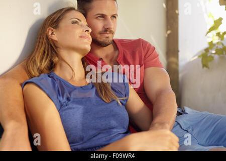 Colpo all'aperto di amare giovane uomo e donna seduta nel loro cortile. Amore giovane seduto rilassato insieme nel Foto Stock