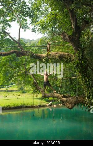 Uomo maturo jumping metà aria nella laguna turchese, Vang Vieng, Laos Foto Stock