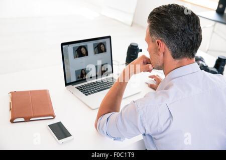 Vista posteriore ritratto di un giovane uomo che utilizza computer portatile al suo luogo di lavoro Foto Stock